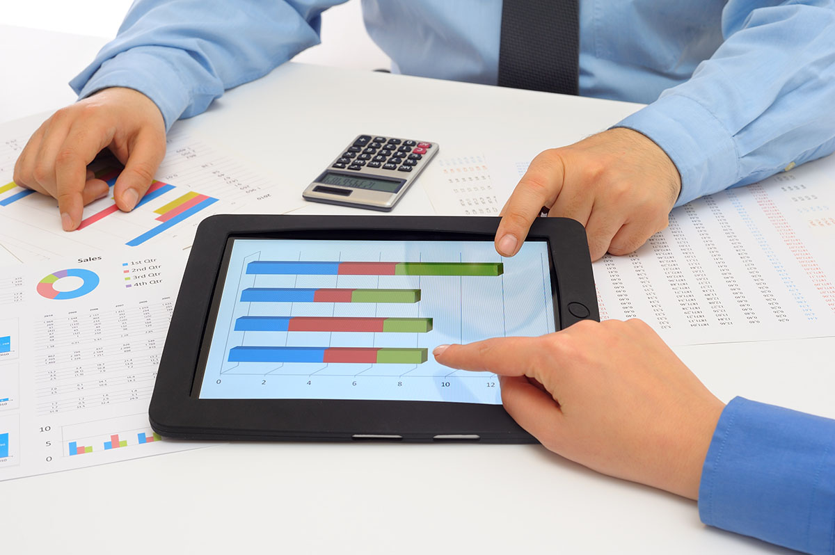 Businessman and businesswoman using digital tablet for the debt service coverage ratio formula