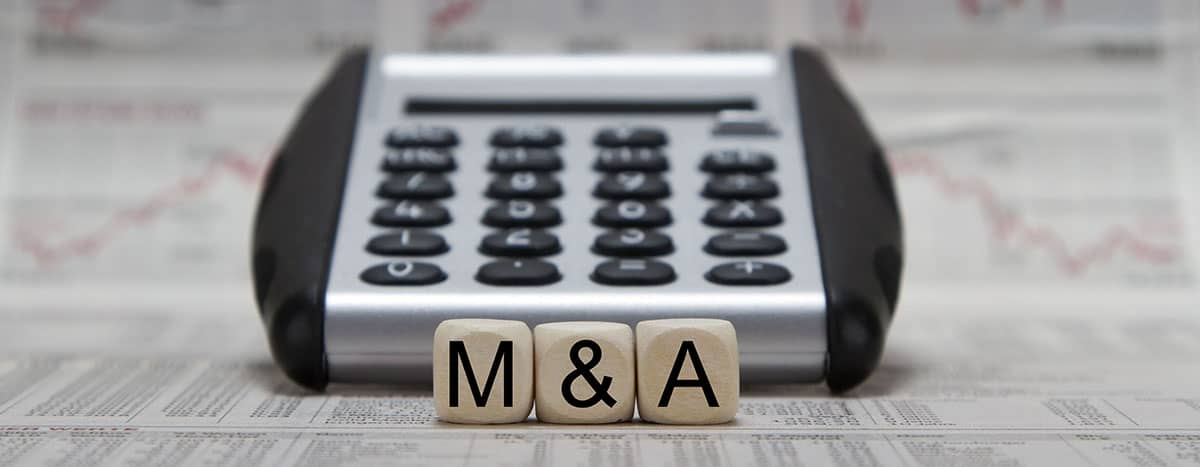 """wooden blocks with """"M&A"""" in front of a calculator"""