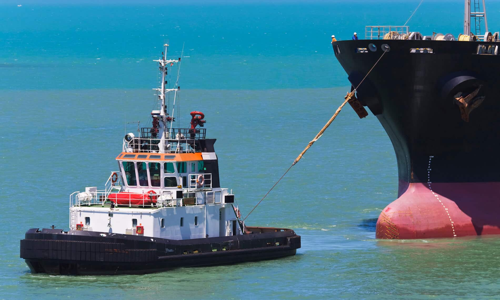 A little tug pulling this huge Cargo Ship behind it, both with shipping loans